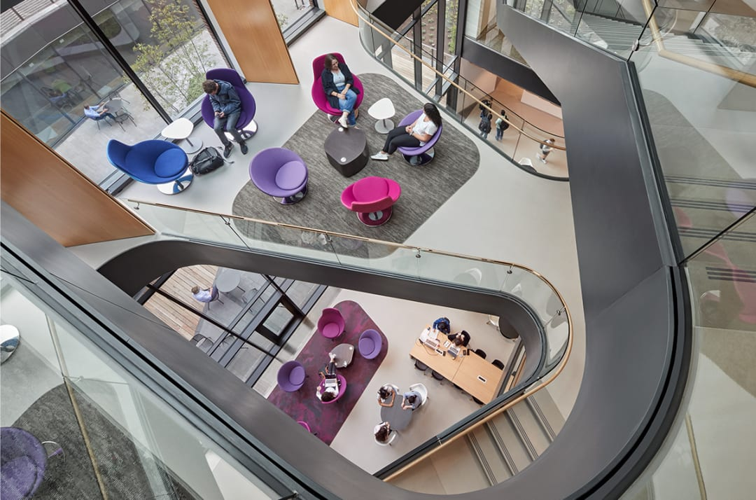 A Winding stair from above with a series of seating areas on the landings with purple and magenta chairs.
