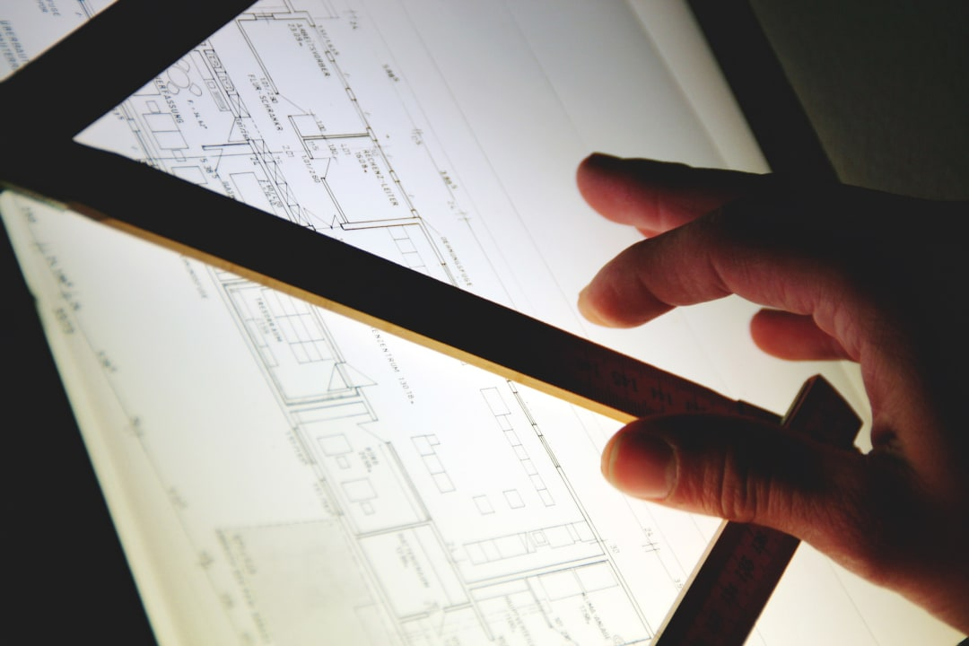 Lightbox with architectural plans, straight edge and architect's hand