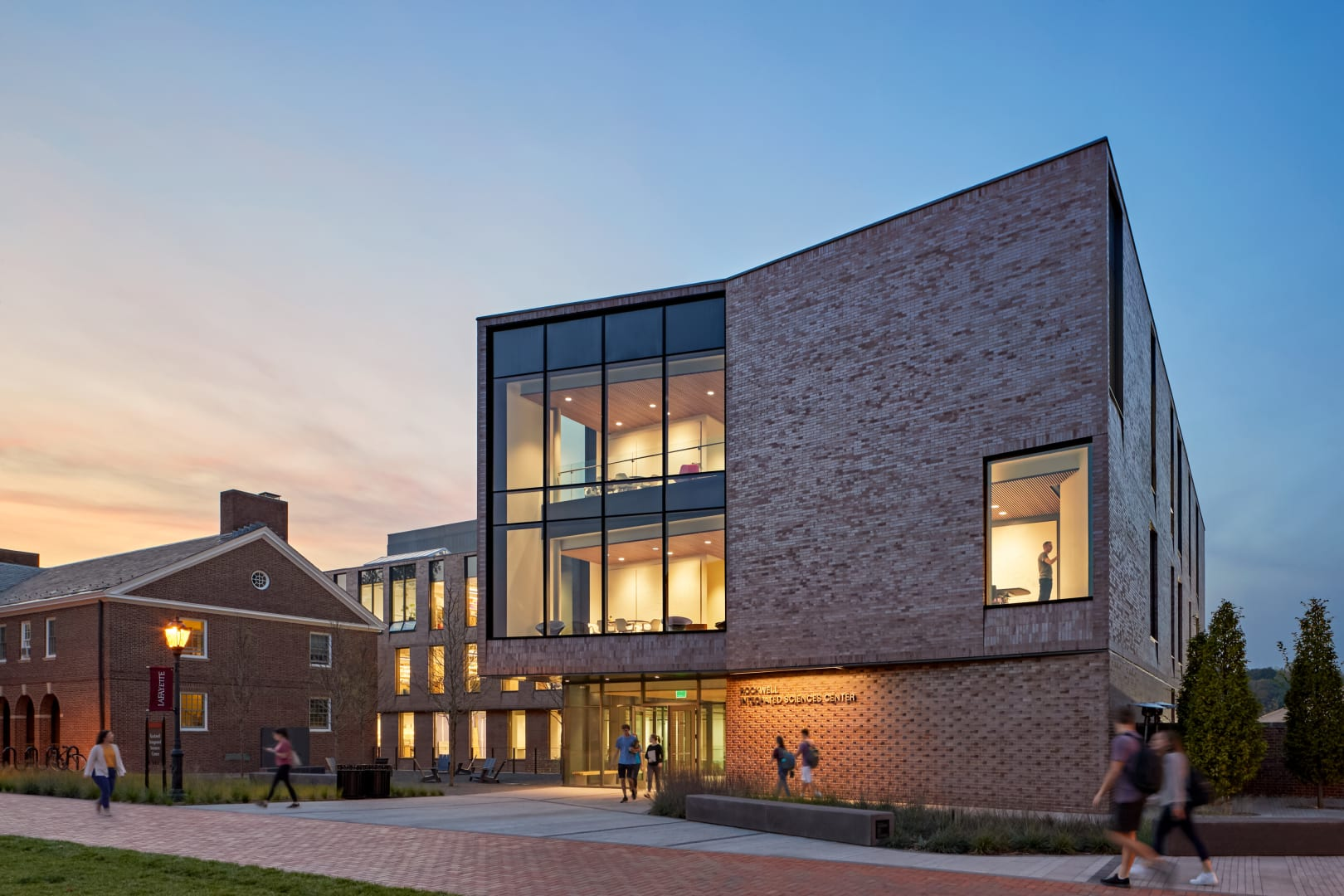The front face of a campus science building. It's exterior marries traditional red brick architecture with large section of modern floor to ceiling windows.