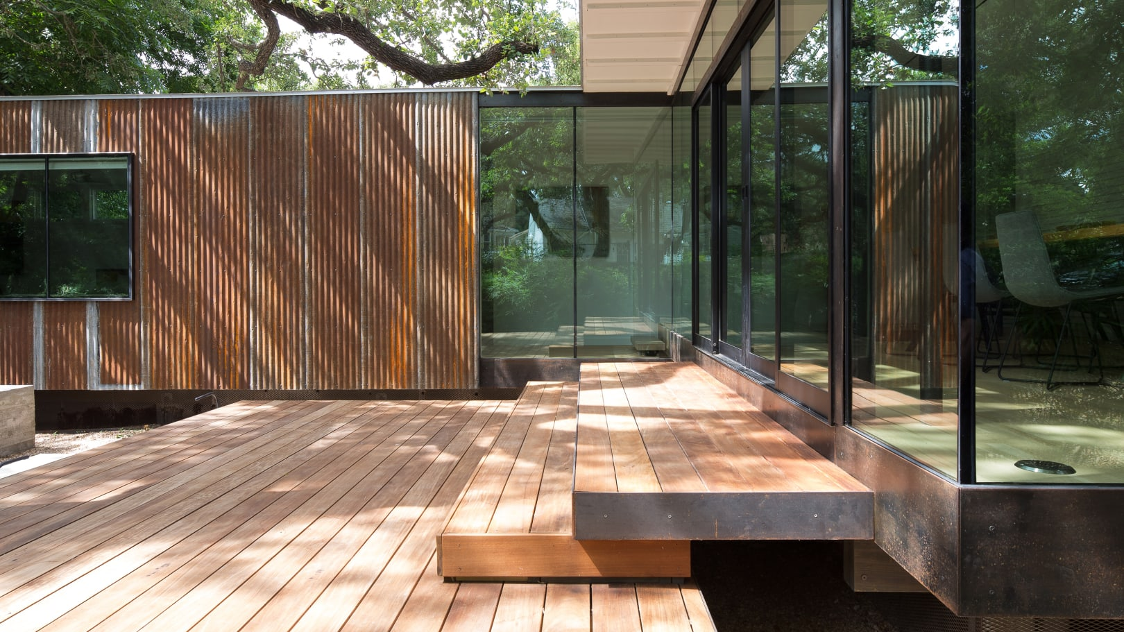 New wood terrace floats over a pea-stone courtyard.