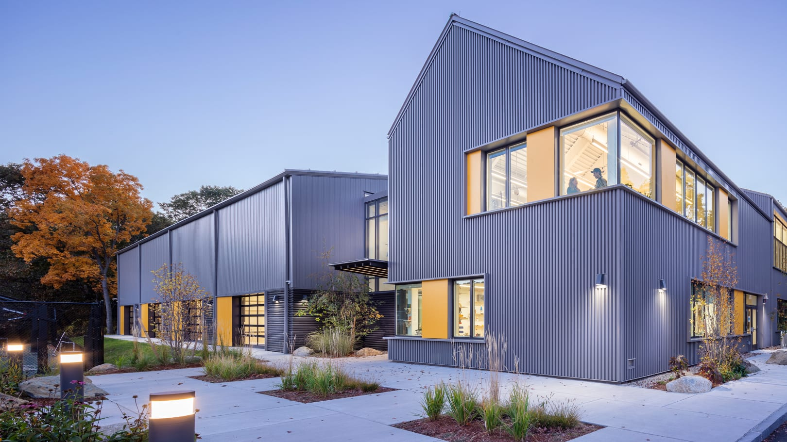 The Barn comprises two buildings: a pre-engineered metal fieldhouse and a stick-built headhouse with 5 STEAM classrooms. The corrugated metal cladding and exposed steel structure provide a design language that bridges the gap.