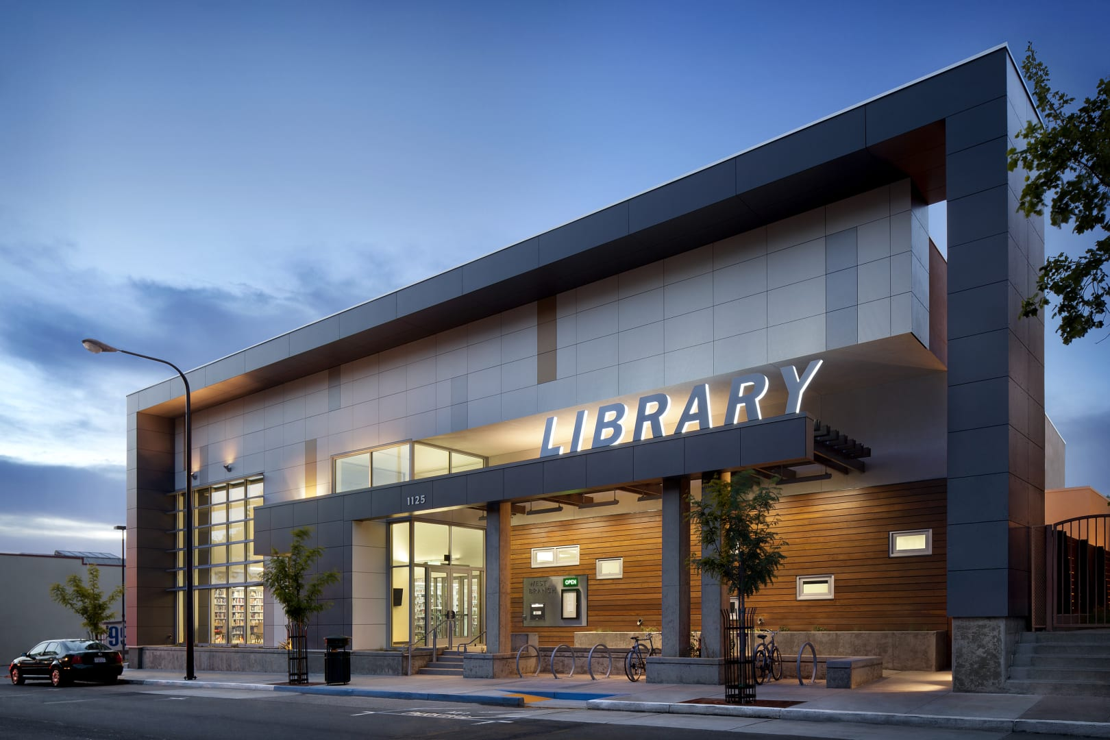 Exterior photo in dusk of the library with gray cladding and wood paneling with backlighting the word library.