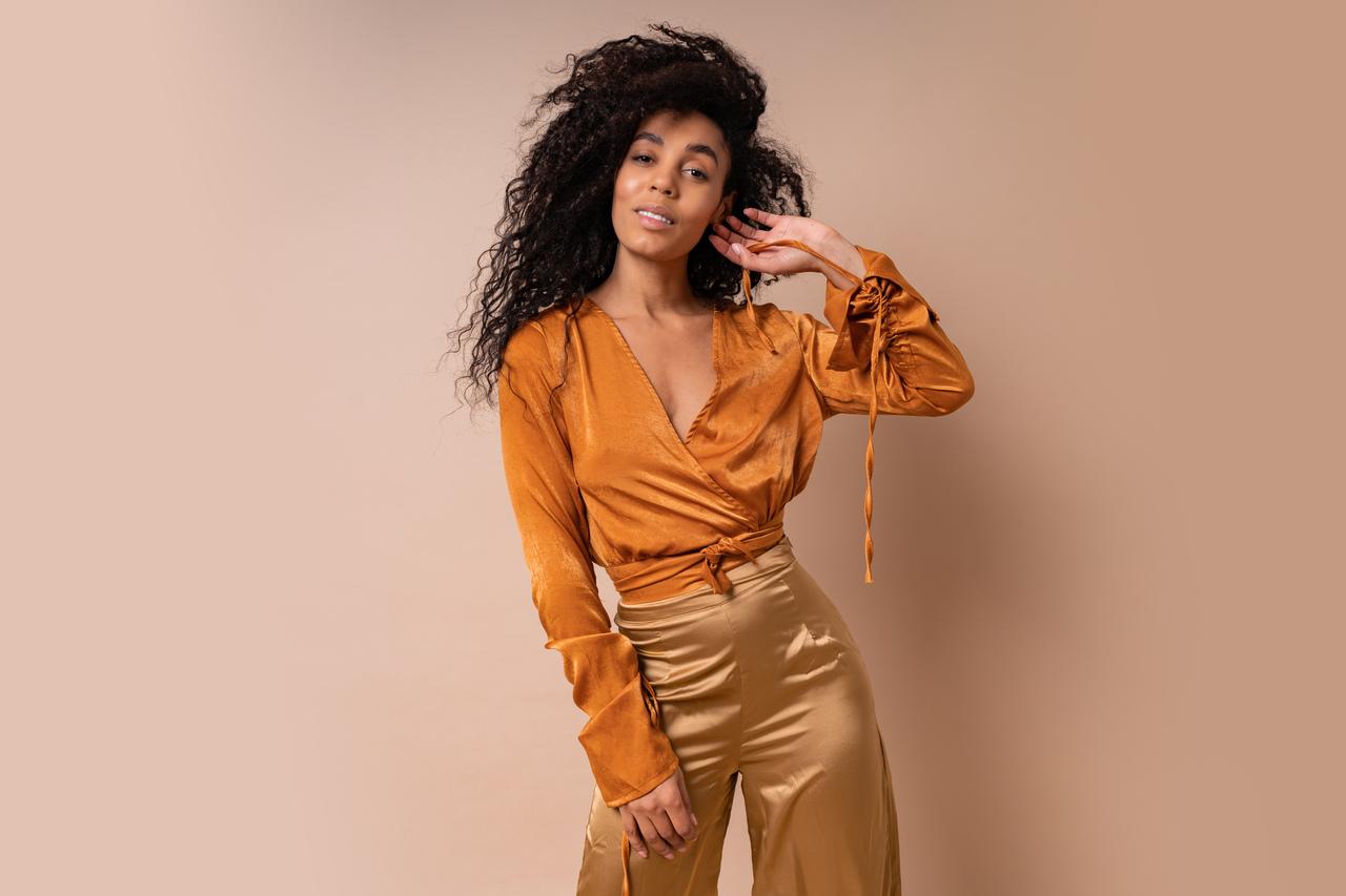 mulher negra vestindo cores que combinam com dourado