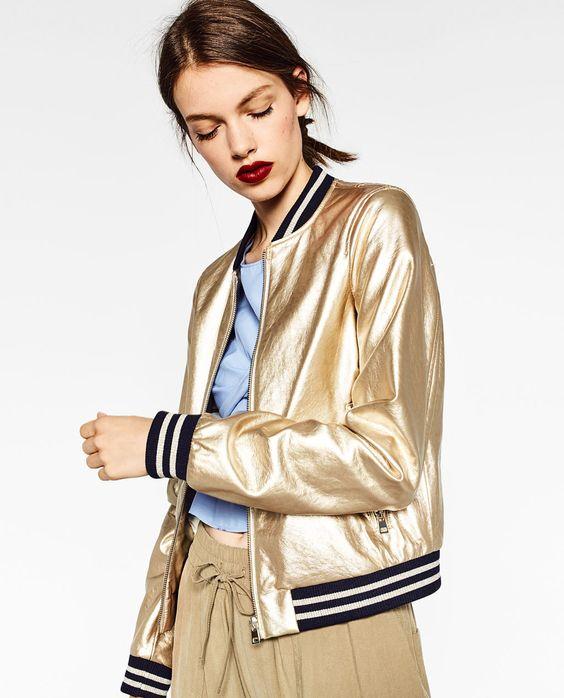 mulher vestindo jaqueta bomber dourada