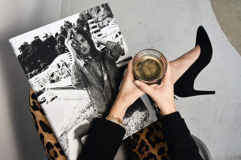 mãos segurando copo e revistas de moda