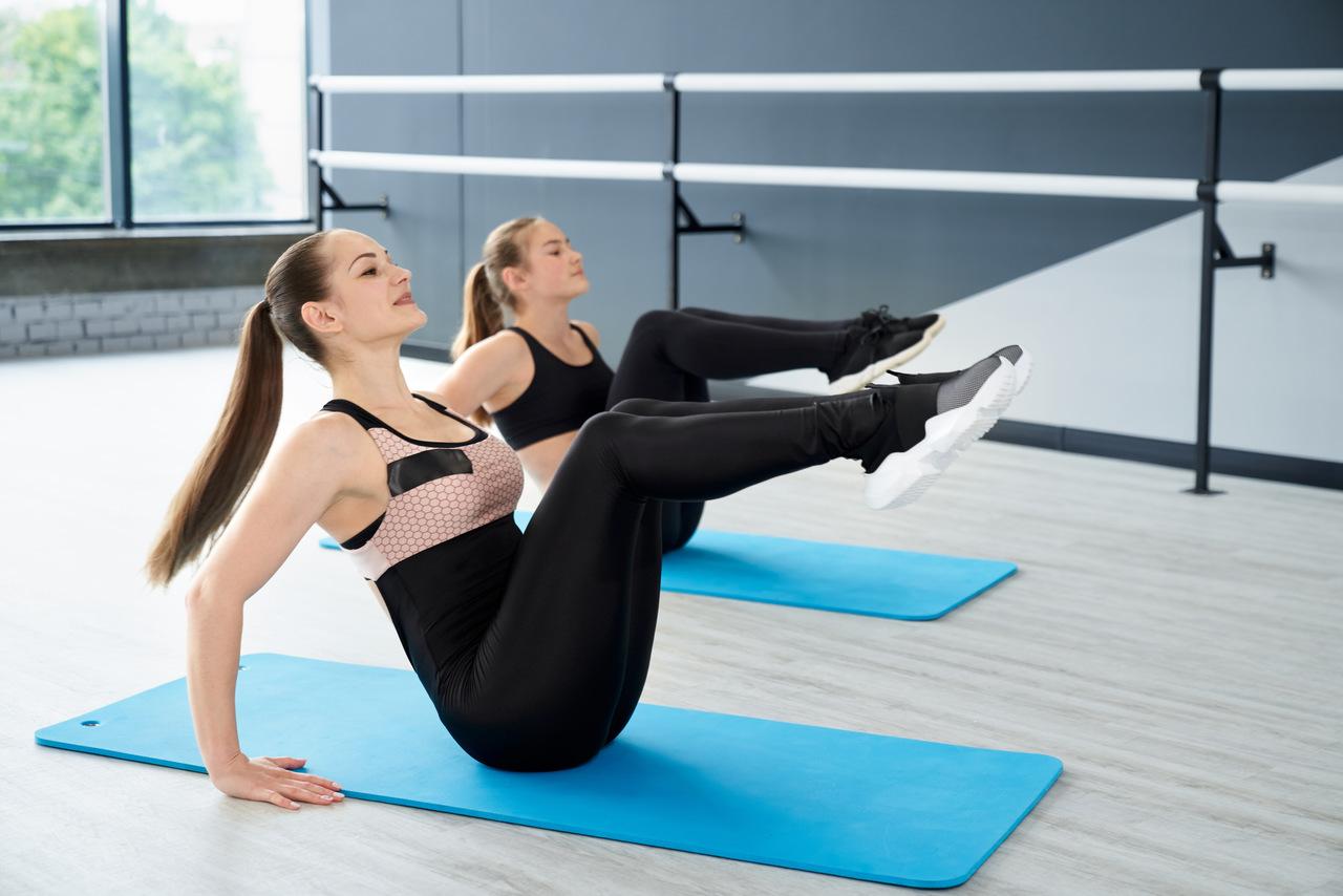 duas mulheres praticando exercícios físicos no colchonete