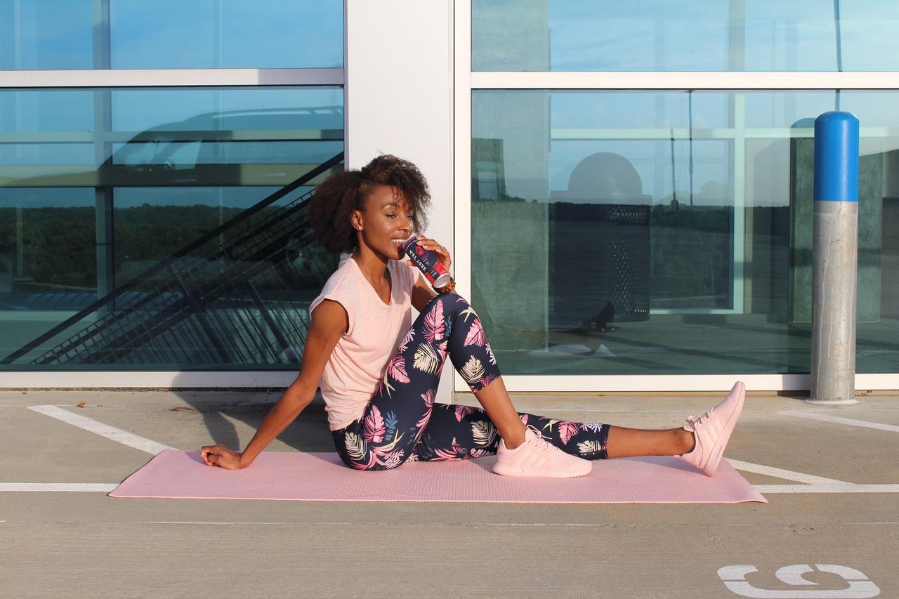 mulher negra sentada no sol vestindo roupas fitness