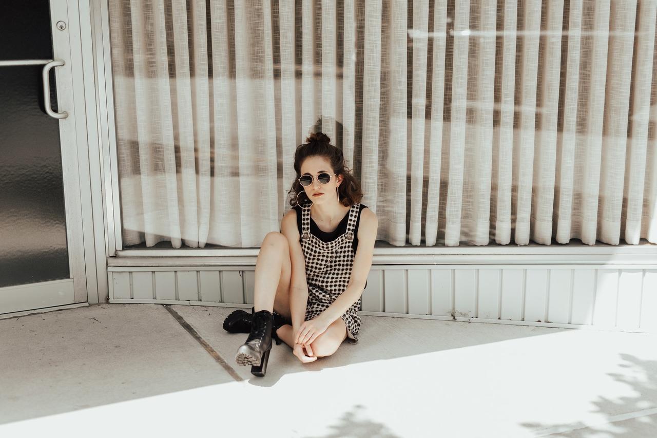 mulher sentada no chão fazendo pose para mostrar o look