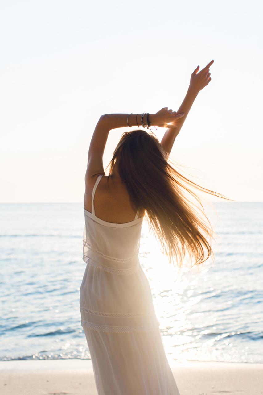 mulher na praia com vestido branco para mostrar as tendências de moda primavera/verão 2021