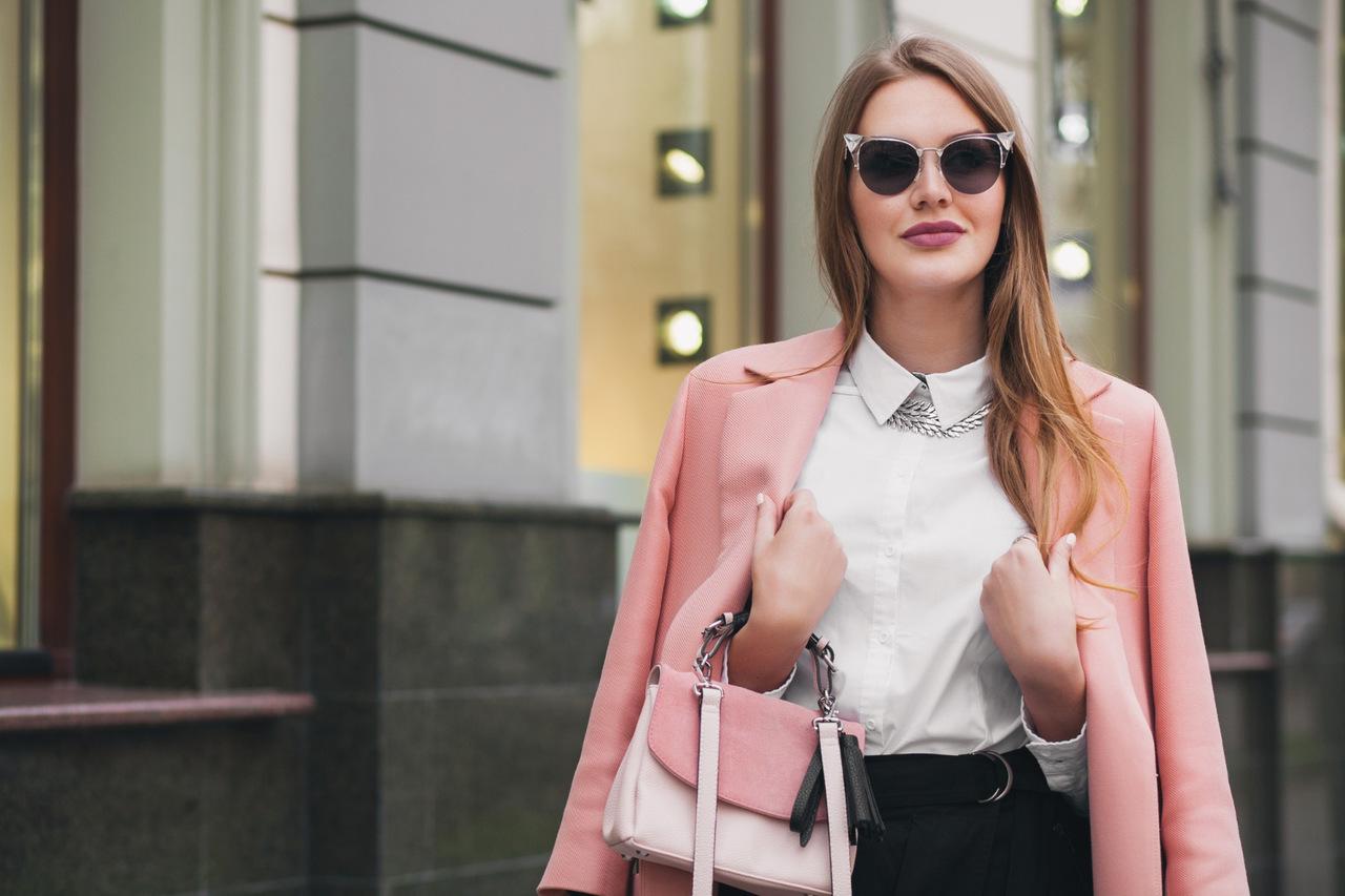 mulher estilosa com óculos de sol, blazer e bolsa para demonstrar como combinar acessórios