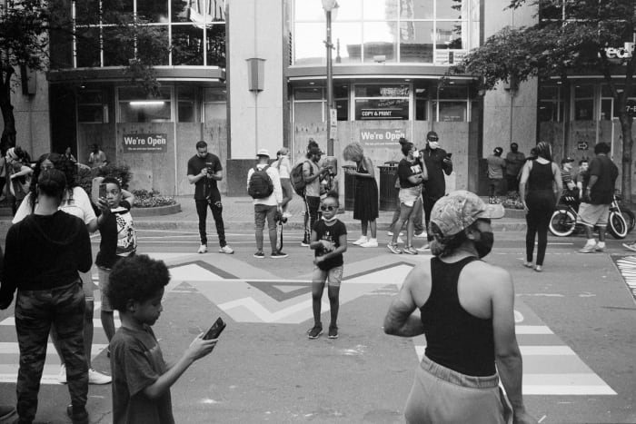 little girl dancing in a crowd viewing black lives matter mural