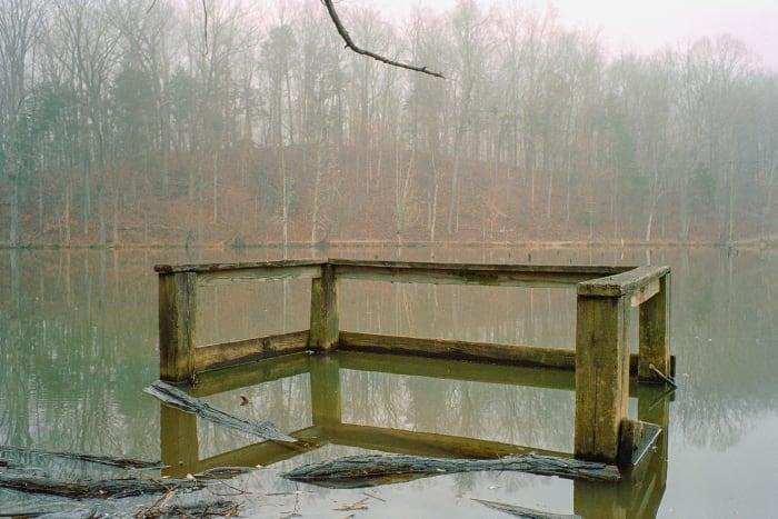 small dock half under murky water in fog