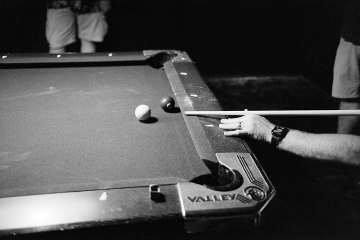 mans arm playing pool