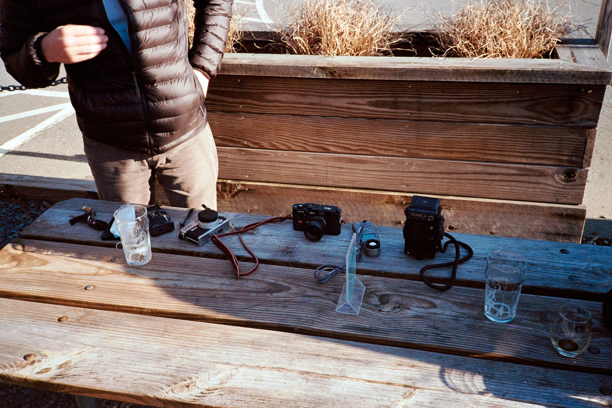 picnic table with various cameras and drinks