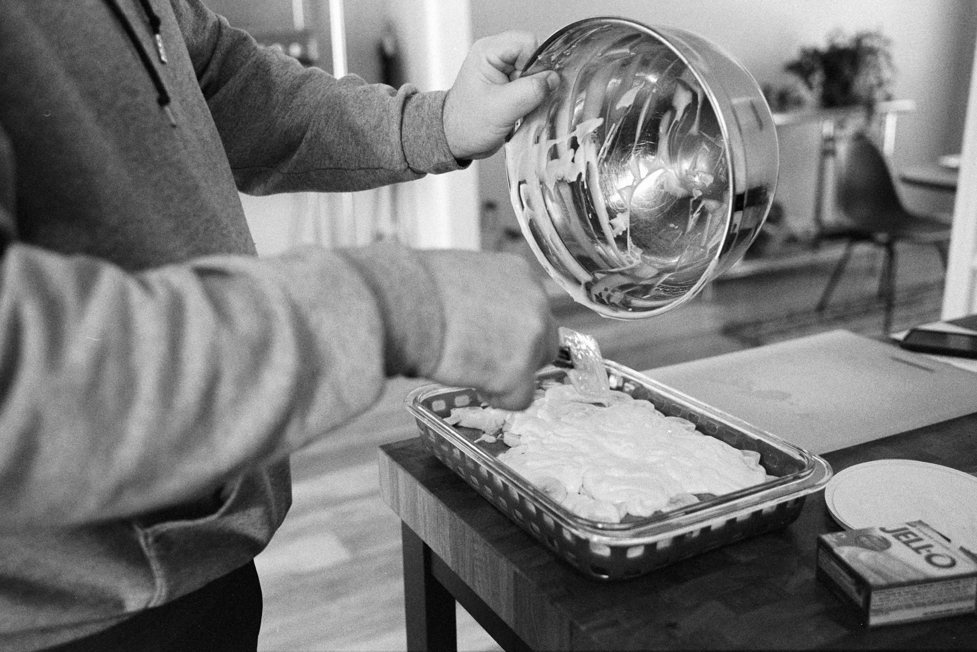 man scooping pudding from a bowl into dish