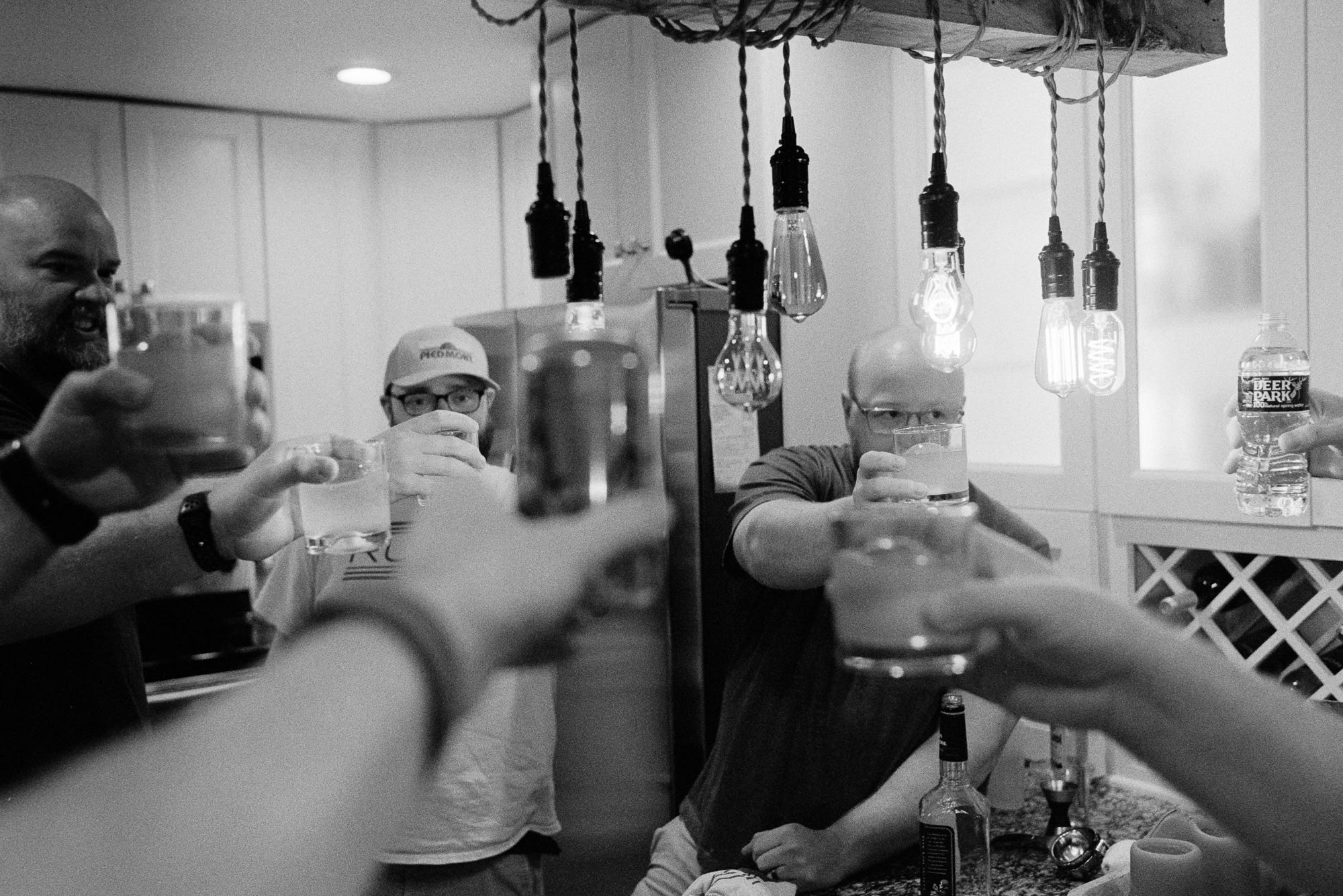 people holding up various drinks in celebration