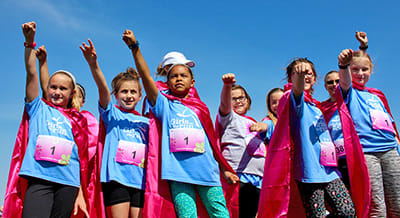 Girls on the Run members show off their capes and running tags at a season ending 5K event.