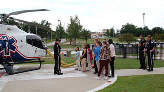 Phil Wilkenson, an Air Methods paramedic, shows the Career Camp students the Staff for Life helicopter based at Lake Regional Health System. Also pictured are Air Methods pilots Daniel Doornink and Caleb Barnes.