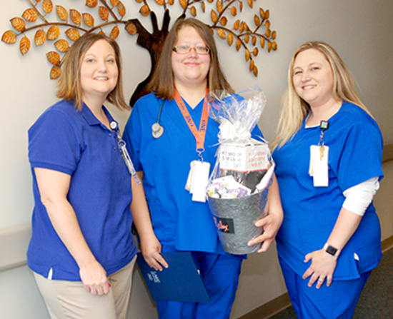 Jaimie Wheat, Med/Surg nurse manager, and Ashley Mikles, unit lead, present Laurie Butz, R.N., with the Mentorship award.