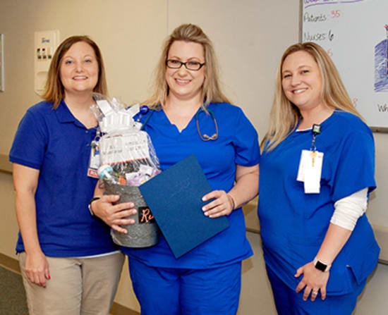 Jaimie Wheat, Med/Surg nurse manager, and Ashley Mikles, unit lead, present Erin Rudner, R.N., with the Rookie of the Year award.