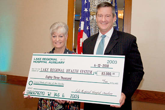 Lake Regional Health System CEO Dane W. Henry accepts a check for $83,000 presented by Jayne Brown, Auxiliary president, on behalf of the Lake Regional Hospital Auxiliary.