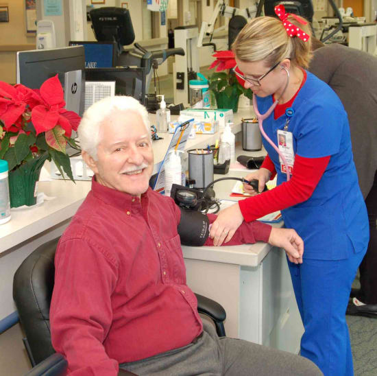 Lake Regional Cardiac Rehab patient Victor Herbert starts his workout with a vitals check from Brianne Long, R.N.