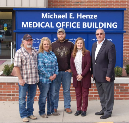 Anthony and Tami Dinwiddie and Daniel Hall of Smokin Trowel Masonry of Eldon stand with Gerri and and Michael E. Henze. Smokin Trowel Masonry donated the brickwork for the exterior sign.