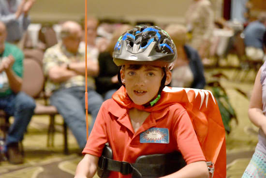 Owen Stark, 9, speeds through his laps around the ballroom on his new Amtryke.