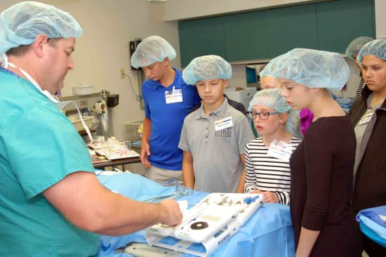Alvin Lawson, a certified surgical tech, explains the uses of various surgical tools to a group of Career Camp students.