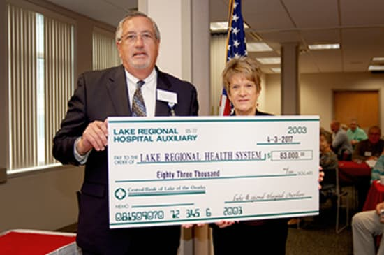 Lake Regional Health System CEO Michael E. Henze accepts a check for $83,000 presented by Auxiliary President Betty Coleman on behalf of the Lake Regional Hospital Auxiliary.
