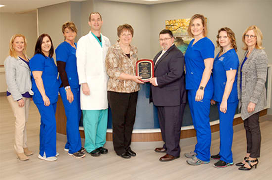 Lake Regional Wound Healing Center receives its Center of Excellence award. Pictured are Laurie Lowther, program director; Amanda Patrickus, LPN; Sharon Jones, R.N.; Justin Shatto, M.D.; Debbie Gentry, R.N., BSN, WOCN, Healogics senior director of Clinical Operations; Mike Dow, PharmD, director of Ancillary Services; Lisa Caudle, R.N.; Rhonda Weaver, R.N.; and Laura Phelps.