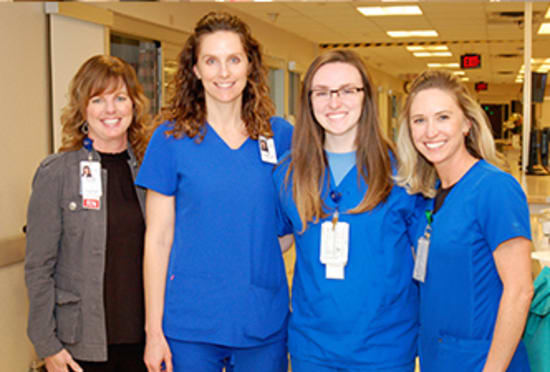 Lindsey Griffin, R.N., center right, receives her Rookie of the Year award from Hunter; Amy Kempf, R.N., Critical Care director; and Erin Whitcomb, R.N., Critical Care manager.