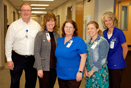 Judy Mahoney, LPN, center, receives the Licensed Practical Nurse of the Year award, from Kevin McRoberts, FACHE, senior vice president of Operations; Hunter; Brandi Kincaid, NP-C, AOCNP; and Marcy Maxwell, Cancer Services director.