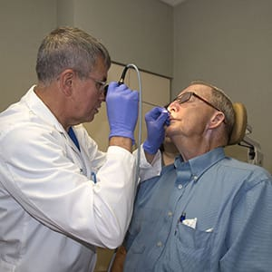 Ear, nose, and throat doctor checking a patient's nose