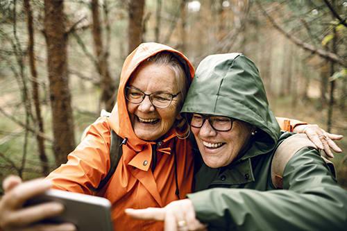 Women hiking in woods taking a selfie