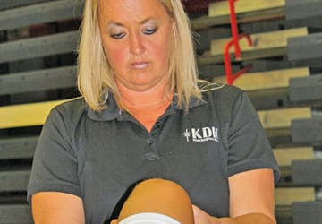 Woman athletic trainer testing knee mobility
