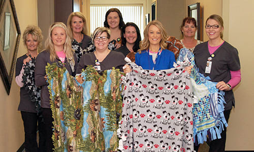 Lake Regional Health System Diagnostic Imaging staff pose with handmade blankets for Lake Regional Cancer Center patients. Pictured are, left to right, Pam Walters RT(R)(M)(QM)(BD); Katelynn Holdt, RT(R)(T)(CT); Karen Bischof RT(R)(MR); Rogetta Meyer, RT(R)(M)(BD); Amanda Blaeuer; Kristy Wood, RT(R)(M); Heather Koch, R.N.; Kari Hartema, CHAA; and Mandy Bargfrede, RT(R)(M).