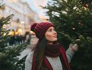 A young woman is standing between two trees in a Christmas tree lot.