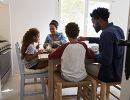 A family of four shares a meal at their kitchen table.