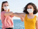 Two teenage girls wearing masks and summer attire bumping elbows.