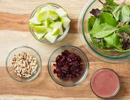 Ingredients for apple salad spread out in bowls.