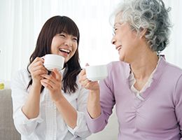 Older and younger woman holding teacups and smiling at each other.
