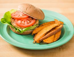 Salmon burger with a side of sweet potato fries.