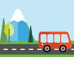 Un bus en la carretera con una montaña en el fondo.