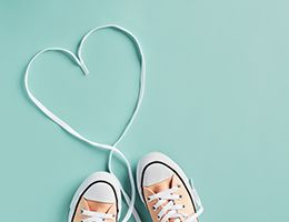 A pair of shoes with laces that are arranged in the shape of a heart.