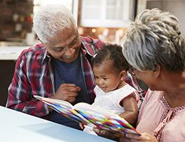 A grandma and grandpa read to their baby granddaughter.
