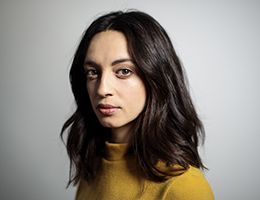 A young woman in a yellow sweater looks at the camera.