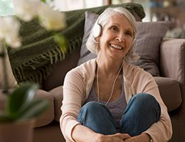 A smiling woman sitting on the floor in a living room with headphones on.
