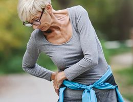 A woman pauses her walk to lean over and press her hip.