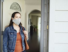 A woman in a face mask walks out her front door.
